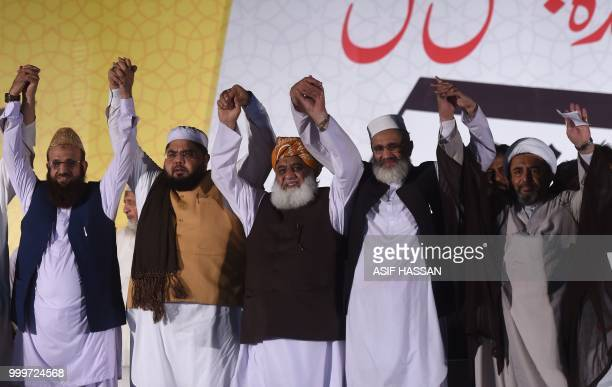 Leaders of Muttahida MajliseAmal a religious parties alliance Maulana Fazlur Rehman SirajulHaq and others raise hands during an election campaign...