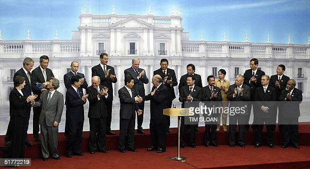 Leaders of the AsiaPacific Economic Cooperation shake hands and applaud after Chilean President Ricardo Lagos delivered the closing speech at the...