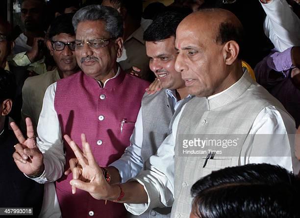 BJP leaders Om Mathur Devendra Fadnavis and Rajnath Singh make victory sign during the legislative meeting at Vidhan Bhavan on October 28 2014 in...