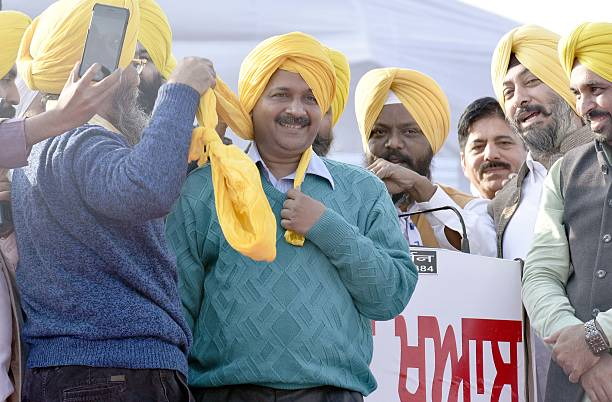 AAP leaders tying the turban to AAP National Convener and Delhi CM Arvind Kejriwal during a `Majha Fateh` rally being organized at Majitha...