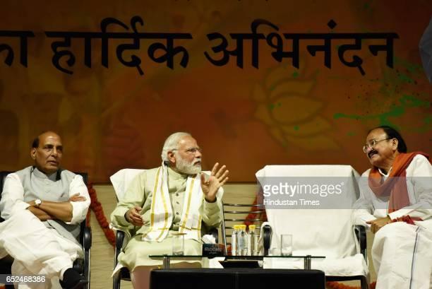 BJP leaders Venkaiah Naidu Rajnath Singh and Prime Minister Narendra Modi with a garland during the Holi Milan celebrations at Delhi BJP Office and...