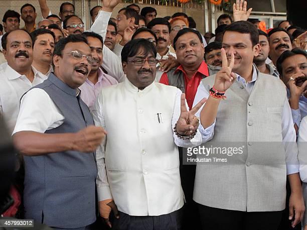 BJP leaders Vinod Tawde Sudhir Mungantiwar and Devendra Fadnavis make victory sign during the legislative meeting at Vidhan Bhavan on October 28 2014...