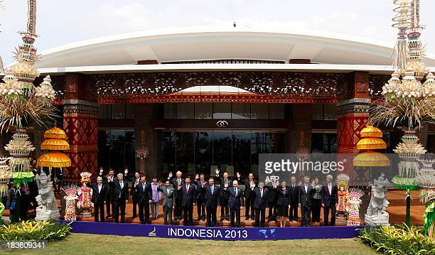 Leaders wave for the traditional leaders' family photo on the final day of the AsiaPacific Economic Cooperation Summit in Nusa Dua on the Indonesian...