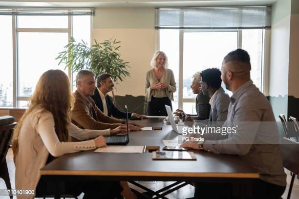 empresaria de liderazgo hablando con colegas en la reunión - equidad de genero fotografías e imágenes de stock
