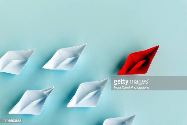 leadership concept - red paper boat followed by white paper boat on blue background - leading stock pictures, royalty-free photos & images