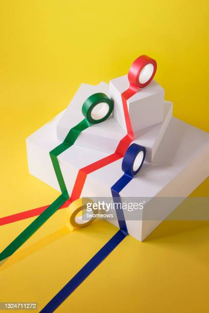 leadership concepts coloured tapes rolling out still life. - competition group stock pictures, royalty-free photos & images