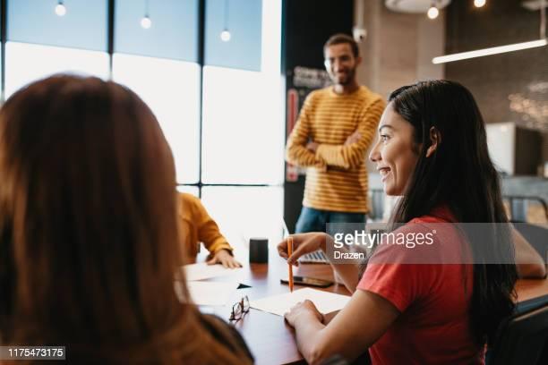 leadership en affaires - femme patron ne prend pas de décisions avec les employés - adulte d'âge moyen photos et images de collection