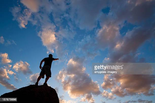 leadership: sunset sky silhouette of man pointing the way