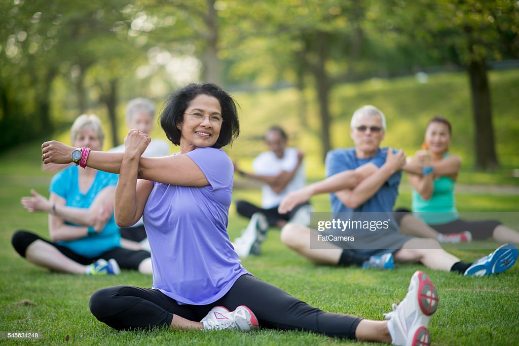 Leading a Senior Fitness Class at the Park : Stock Photo
