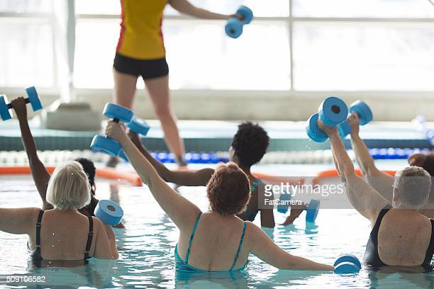 leading a water aerobics class - adult stock pictures, royalty-free photos & images