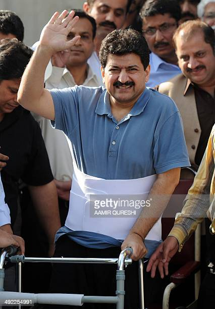 Leading Pakistani TV journalist Hamid Mir who survived an April attack by gumen in Karachi waves as he leaves the Supreme Court in a wheelchair after...