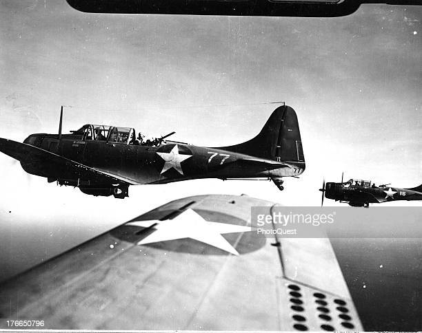 Leading the flight of Bulldog dive bombers is Major Claude J. Calson, Jr., USMC, near Guadalcanal, August 22, 1943. His plane, No. 77, is shown...