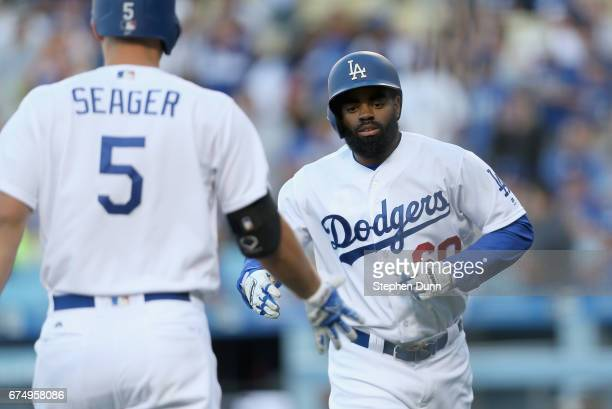 Leadoff batter Andrew Toles of the Los Angeles Dodgers is greeted by on deck batter Corey Seager as he returns to the dugout after hitting a solo...