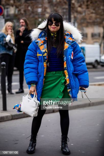 Leaf Greener wearing a blue jumper green mini skirt black boots white bag and blue puffed jacket is seen in the streets of Paris before the Acne...