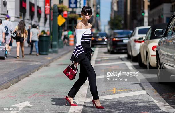 Leaf Greener wearing off shoulder top and red heels outside Tome on September 11 2016 in New York City