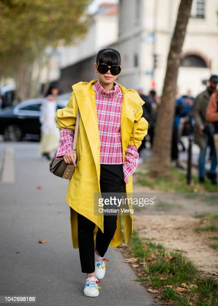 Leaf Greener wearing yellow rain coat checked plaid turtleneck white sneaker is seen outside Loewe during Paris Fashion Week Womenswear Spring/Summer...