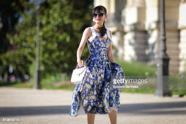 Leaf Greener wears sunglasses, a blue flower print dress, a white bag, white shoes, outside the Giambattista Valli show, during Paris Fashion Week -...
