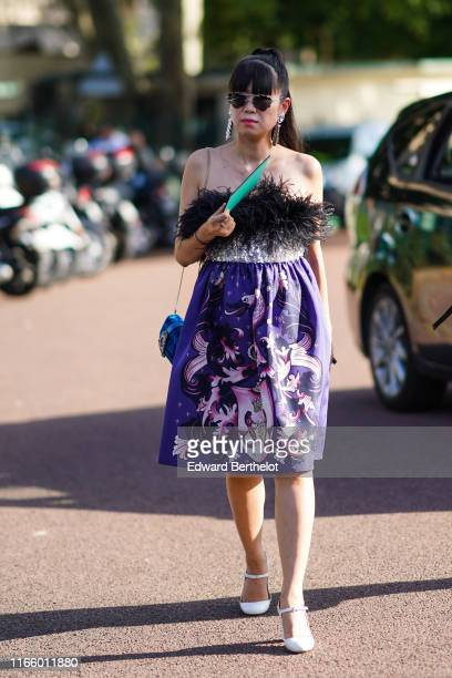 Leaf Greener wears sunglasses, a earrings, a fluffy off-shoulder dress with a printed animal, a blue bag, white shoes, outside Miu Miu Club 2020, on...