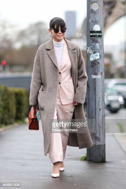 Leaf Greener wears sunglasses a white turtleneck pull over a pink blazer jacket pink suit pants a gray wool coat an orange bag and pink shoes outside...