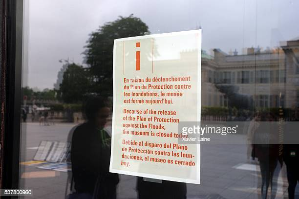 A leaflet informs about the closed Orsay Museum as water rises near the area of the Louvre Museum as the Seine river's embankments overflow on June 3...