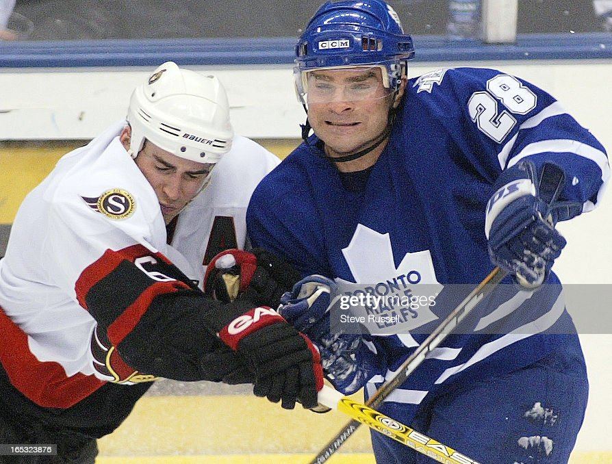 TORONTO MAPLE LEAFS---01/31/04---Tie Domi, wearing a visor, checks Wade Redden as the Toronto Maple  : News Photo