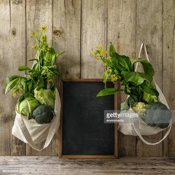 再利用可能なコットン バッグ、古い木製ボード上、途中で黒板のいずれかの側にぶら下がっている緑の葉野菜の背景を壁します。