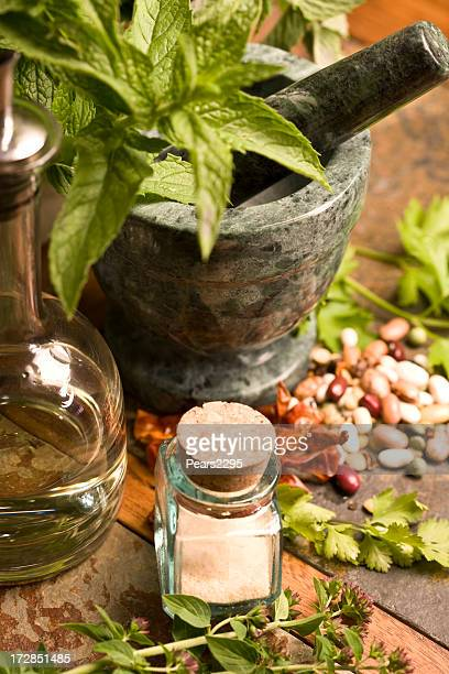 Leafy greens in stone mortar and pestle small jar in front