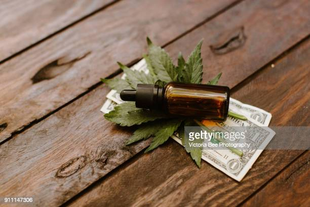 leafy medical cannabis plant with marijuana buds with oil over wooden background - cannabis oil stock photos and pictures