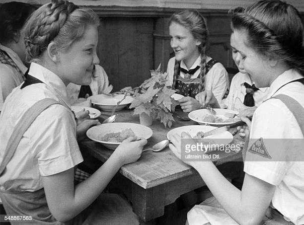 League of German Girls girls at a meal in a communal accommodation of the 'Kinderlandverschickung' Maedchen Zoepfe hochgesteckte Hochfrisur undated...