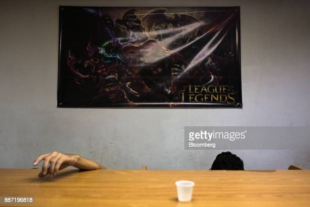 A League of Legends poster hangs above people playing video games at a cybercafe in Caracas Venezuela on Tuesday Nov 28 2017 Crisiswracked...