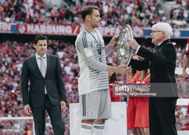 League President Dr. Reinhard Rauball hands over the trophy Meisterschale to goalkeeper Manuel Neuer of FC Bayern Muenchen next to DFL CEO Christian...