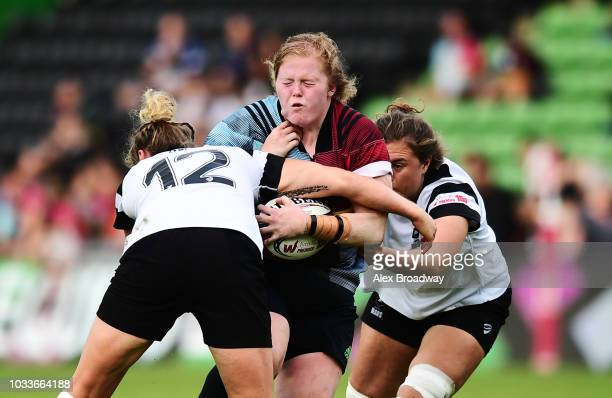 Leah Lyons of Harlequins Ladies is tackled by Amber Reed and Holli Cunningham of Bristol Bears Women during the Tyrrells Premier 15s match between...