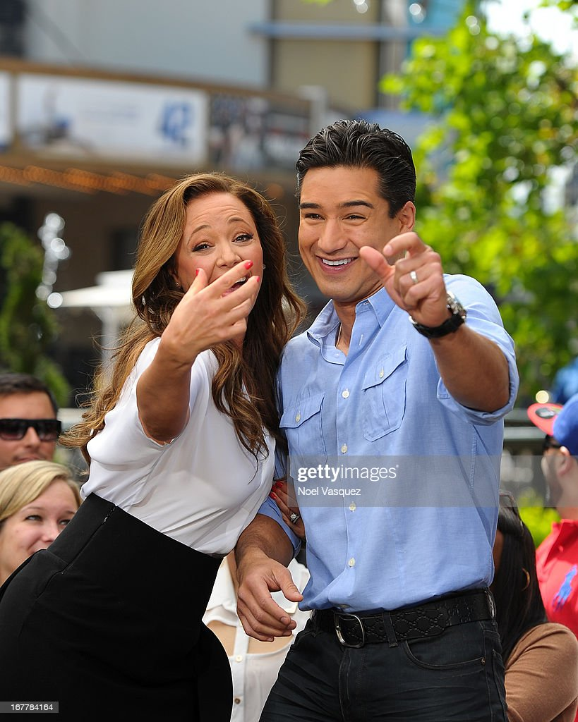 Leah Remini (L) and Mario Lopez pose together at 'Extra' at The Grove on April 29, 2013 in Los Angeles, California.