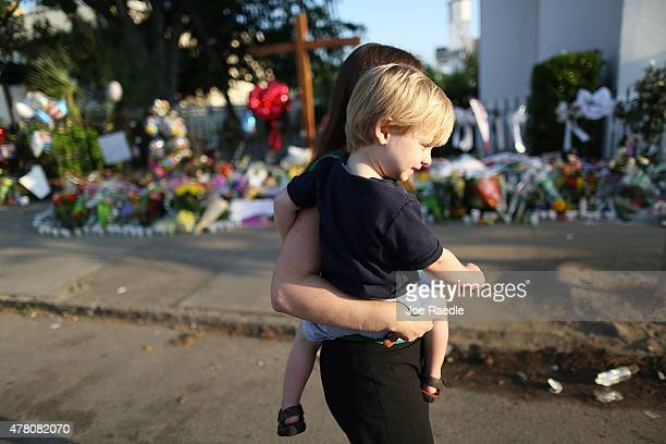 Leah Schonfeld carries her son Carter Schonfeld as they pay their respects in front of the Emanuel African Methodist Episcopal Church after a mass...
