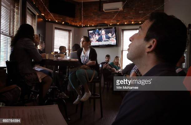 Leah Thrum joins patrons at Shaw's Tavern to watch former FBI Director James Comey testify before the Senate Intelligence Committee June 8, 2017 in...