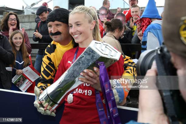 Leah Williamson poses with the trophy with her dad who is dressed as David Seaman during the Women's Super League match between Arsenal Women and...