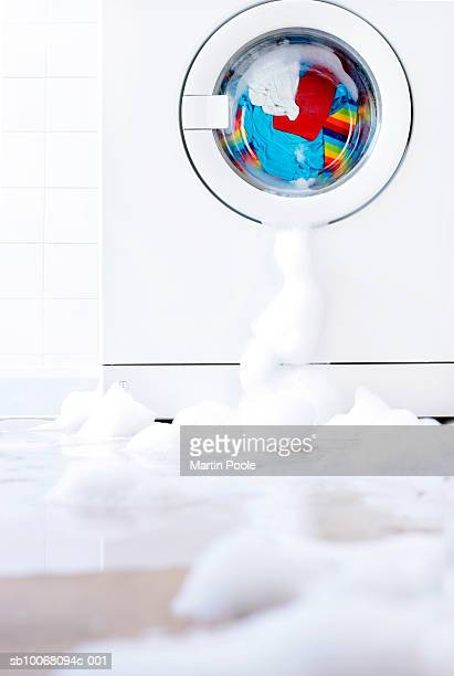 Leaking washing machine surrounded by bubbles