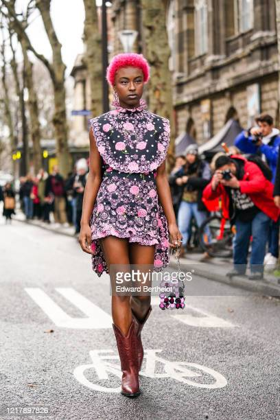Lean Chihiro artist and singer wears pink metallic earrings a black and pink floral print sleeveless dress brown leather cowboy boots a sequined bag...