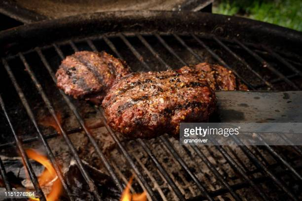 lean healthy hamburgers grilled on an outdoor charcoal grill with flames - juicy stock pictures, royalty-free photos & images