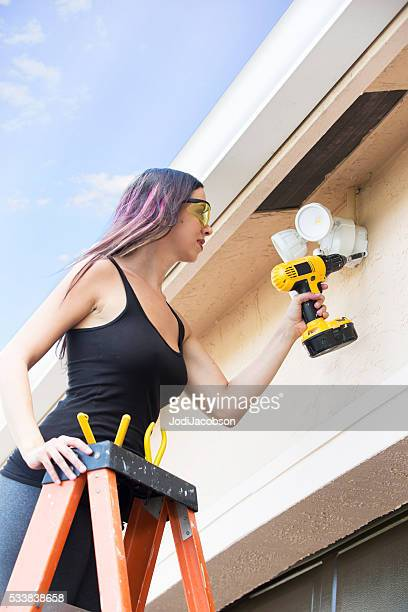 'Lean in'- Real female electrician installing outside lighting