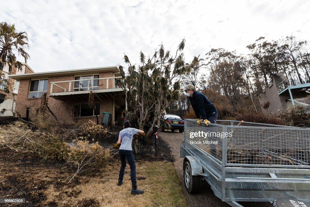 Lean Tong and (R) Jack Morris clean up at their family home, which narrowly escaped the devasation in much of their street on March 23, 2018 in Tathra, Australia. A bushfire which started on 18 March destroyed 65 houses, 35 caravans and cabins, and damaged 48 houses. Preliminary investigations have found that power lines were the likely cause of the fire, raising questions about the maintenance of power infrastructure by Essential Energy, which is owned by the NSW government.