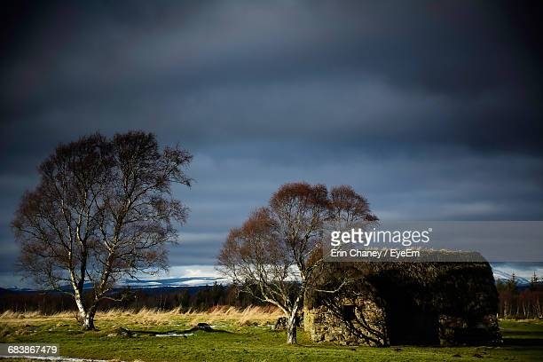 Leanach Cottage On Field Against Cloudy Sky At Scottish Highlands
