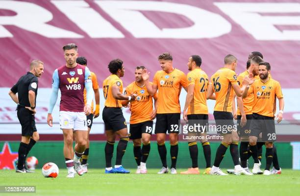 Leander Dendoncker of Wolverhampton Wanderers celebrates with his team mates after scoring his team's first goal as Jack Grealish of Aston Villa...