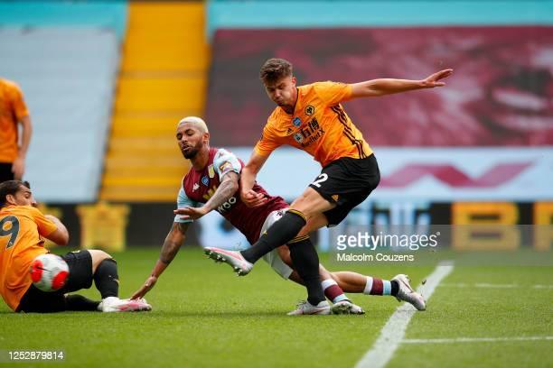 Leander Dendoncker of Wolverhampton Wanderers shoots past Douglas Luiz of Aston Villa to score the first goal during the Premier League match between...