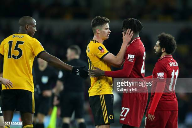 Leander Dendoncker of Wolves hugs Divock Origi of Liverpool after the final whistle in the Emirates FA Cup Third Round match between Wolverhampton...