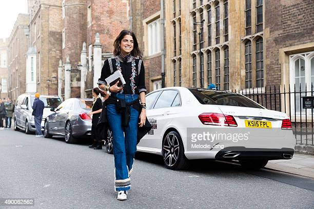 Leandra Medine of Manrepeller enters the Simone Rocha in a black embroidered floral turtleneck Racil jacket around her waist high waisted flaired...