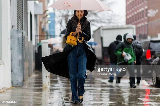 Leandra Medine wearing umbrella a black raincoat and blue denim jeans seen outside Rodarte during New York Fashion Week Women's Fall/Winter 2016 on...