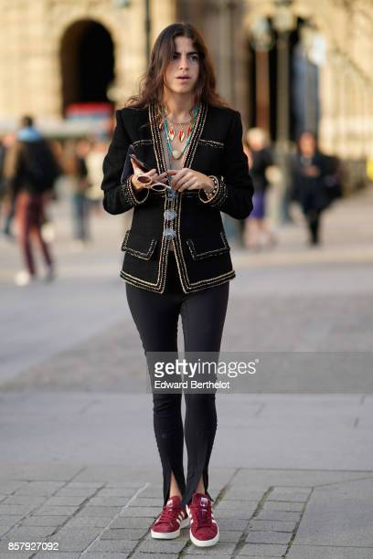 Leandra Medine wears a black jacket with golden borders black pants red sneakers shoes outside Louis Vuitton during Paris Fashion Week Womenswear...