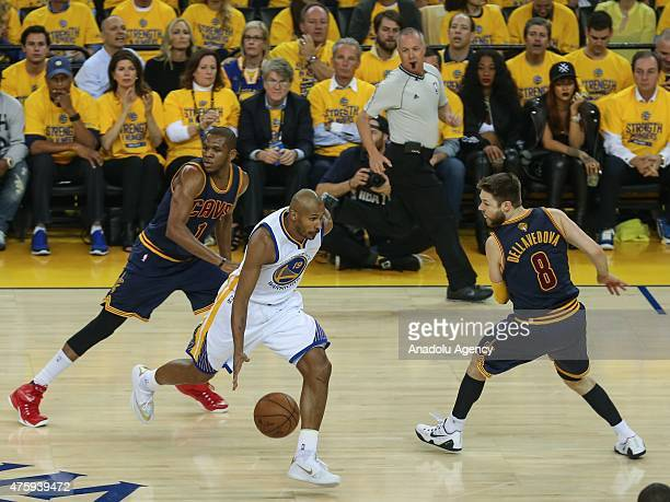 Leandro Barbosa of the Golden State Warriors dribbles the ball against James Jones and Matthew Dellavedova of the Cleveland Cavaliers during Game One...