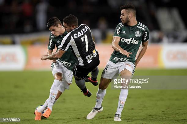 Leandro Carvalho of Botafogo struggles for the ball with Diogo Barbosa and Bruno Henrique of Palmeiras during the match between Botafogo and...